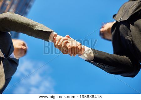 Handshake of partners and blue sky above