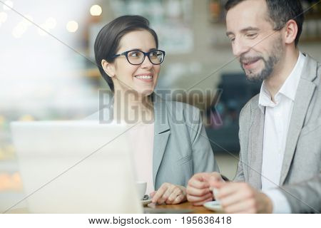 Business professionals sitting in cafe and having talk