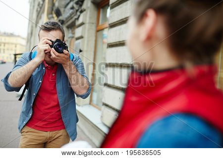 Young man with photocamera shooting his girlfriend on tour