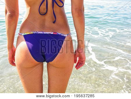 Summer beach concept. Sexy woman buttocks on the beach background. Sexy summer woman body. White sand blue sky and crystal sea of tropical beach.