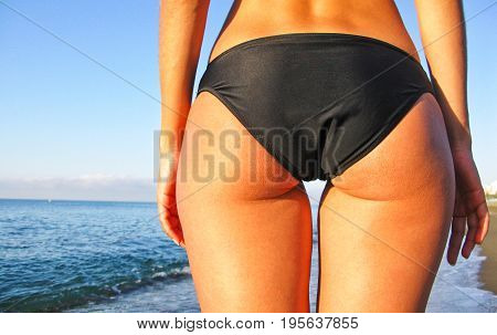 Summer beach concept. Sandy woman buttocks on the beach background. Sexy summer woman body. White sand blue sky and crystal sea of tropical beach.