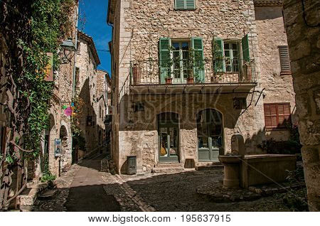 Saint-Paul-de-Vence, France - July 13, 2016. Alley with square, stone houses and fountain in Saint-Paul-de-Vence, stunning medieval town completely preserved. In Provence region, southeastern France
