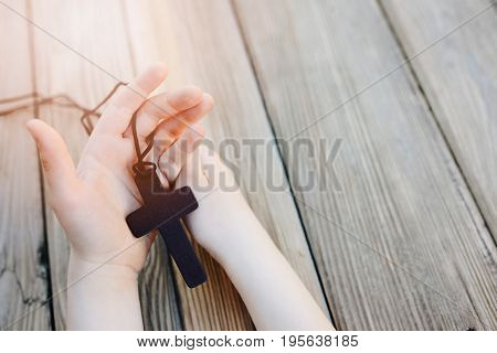 Little Childs Hands Holding Wooden Rosary