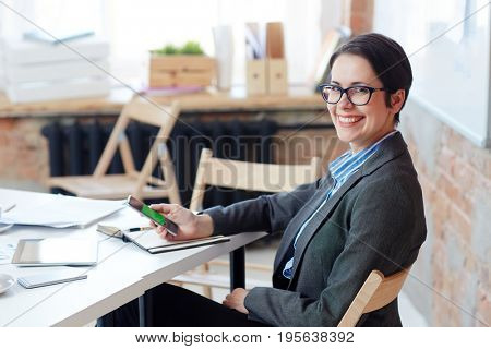 Female broker with smartphone sitting by workplace