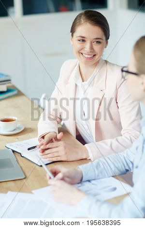 Young accountant listening to co-worker during talk