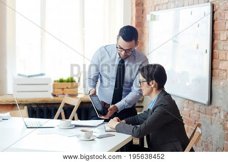 Two contemporary economists watching online video about financial companies