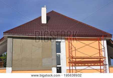 Roofing Construction. Roof Repair. Stucco and painting house wall during renovation with Soffit installation. Remodeling Home with painting house wall.