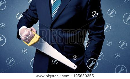 Young serious businesman holding tool with wrench icons around