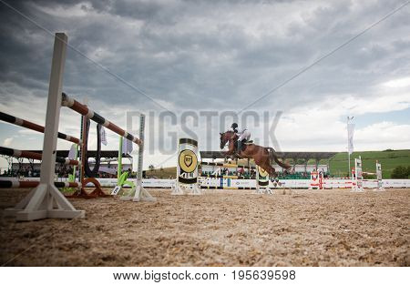 TURDA, CLUJ, ROMANIA - June 29, 2017: An unidentified competitor jumps with his horse at the Salina Equines Horse Trophy , June 29, 2017 in Turda, Cluj, Romania