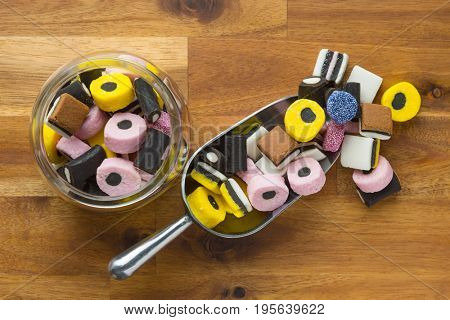 Mixed liquorice candies in scoop on wooden table.