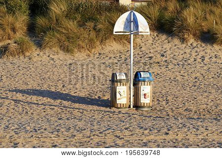 DE PANNE BELGIUM - JULY 02 2017:Two garbage bin for recycling on sand at the beach of De Panne in Belgium