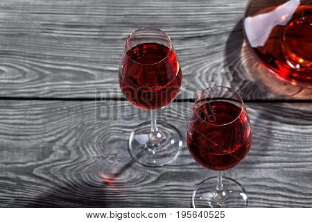 Decanter and two glasses of red wine on a wooden table. Shooting from the top.