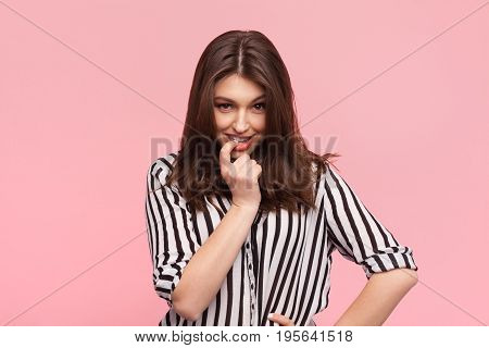 Young brunette in striped shirt biting finger and looking flirty at camera on pink.