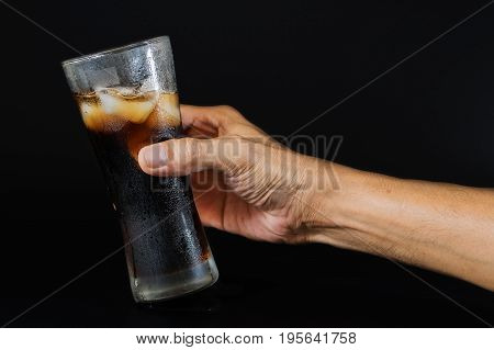 Hand of a man holding a cola glass with ices over black background-Food and drink industry and celebrations concepts.