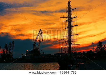 VARNA BULGARIA - MAY 24 2017: Sailboat and port cranes in Varna commercial harbor in sunset