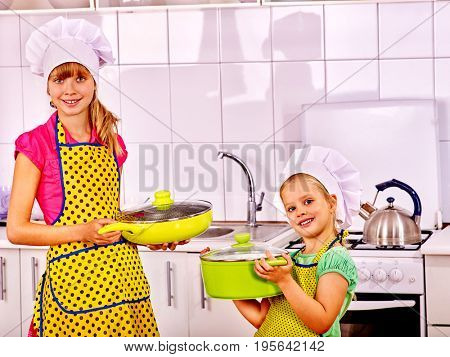 Children cooking at home kitchen. Girl in chef hat with pan and saucepan going to food preparation.
