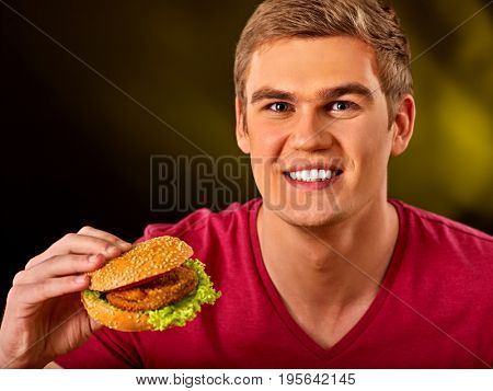 Man eating hamburger. Student consume fast food. Boy bite of very big burger. Boy trying to eat lot of junk. Advertise fast food on black background.