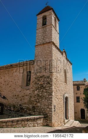 View alley and church with stone steeple tower in Saint-Paul-de-Vence, a lovely well preserved medieval hamlet near Nice. Located in Alpes-Maritimes department, Provence region, southeastern France