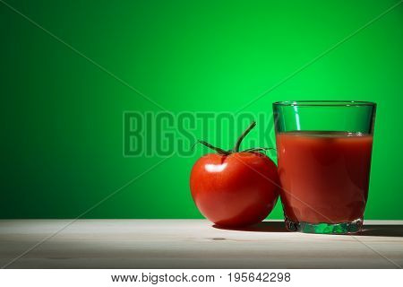 Glass of tomato juice and a tomato on a wooden table with a green background. Summer harvest. The concept of healthy food.