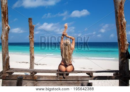 Beautiful blonde woman in the knitted brown bikini sitting on the old wooden bench on the lonely beach with turquoise water and white sand. Zanzibar. Nungwi.