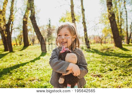 Little girl embracing plush toy and laughing while looking away on background of park.