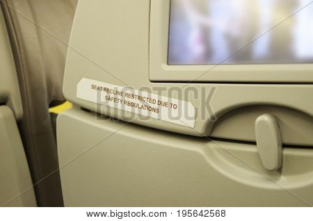 Seat on side of emergency door with the warning message that the seat does not recline by safety regulations
