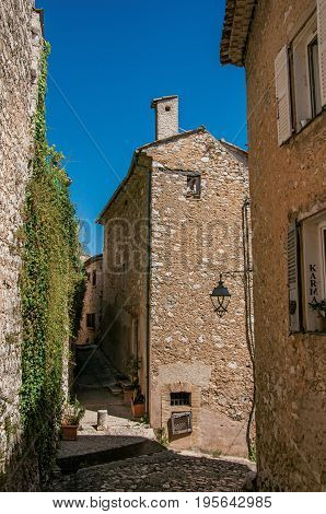 Saint-Paul-de-Vence, France - July 13, 2016. Stone house with lamp and bindweed in the Saint-Paul-de-Vence village, stunning medieval town completely preserved. In Provence region, southeastern France