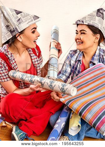 Repair home women holding bank with paint for wallpaper. Elderly mother and daughter renovation apartment on isolated. Home renovation.Good relationship between mother and adult daughter.