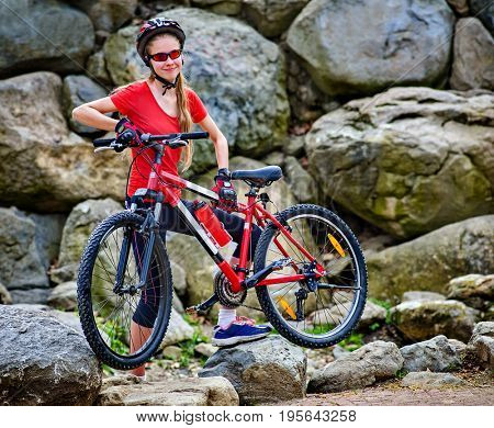 Woman on bicycle ride mountain. Girl traveling in summer park. Early morning cycling person . Sport trip is good for health. Girl gathered in hike mountains and carries her bicycle through stones.