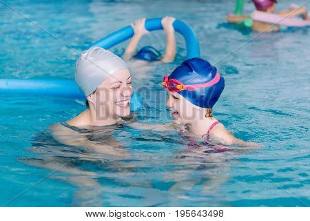 Swimming lesson for children on indoor swimming pool toned image