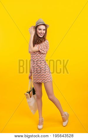 Young smiling girl in dress and straw hat posing with bag in hands on yellow.