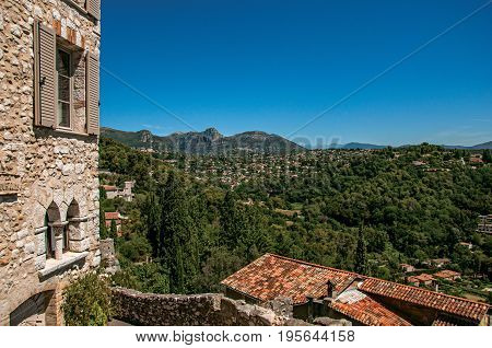 Panoramic view of hills and facade of building in Saint-Paul-de-Vence, a lovely well preserved medieval hamlet near Nice. Located in Alpes-Maritimes department, Provence region, southeastern France