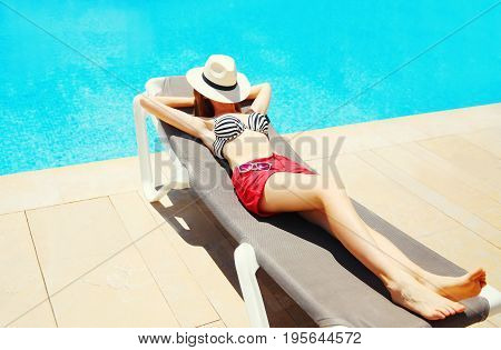 Summer Holidays - Woman Lying Resting On A Deckchair Over A Blue Water Pool Background
