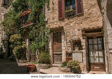Alley view with wooden doors and plants in Saint-Paul-de-Vence, a lovely well preserved medieval hamlet near Nice. Located in Alpes-Maritimes department, Provence region, southeastern France