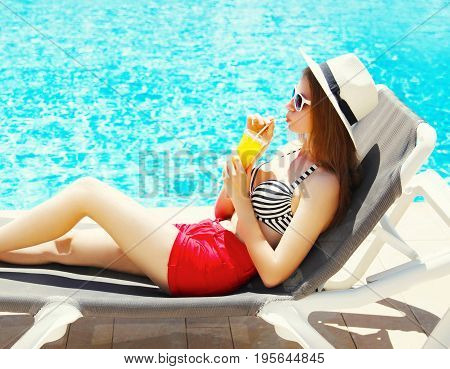Luxury Woman Drinks Juice From Cup At Summer On A Deckchair Over A Blue Water Pool Background