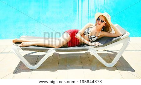 Summer Holidays - Pretty Woman Lying On A Deckchair Over A Blue Water Pool Background