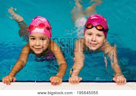 Two little girls on indoor swimming pool toned image