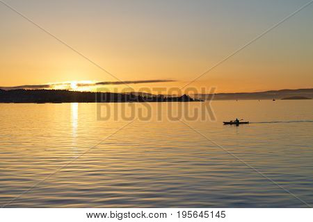 A man in silhouette kayaks across Oslofjord at sunset.