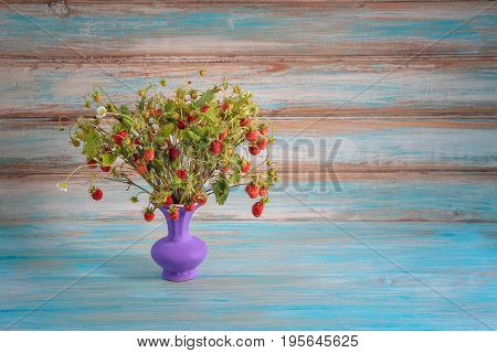 Bouquet of wild strawberries in a vase on a blue background. The concept of summer, sunshine, heat. Studio, plenty of space for text.