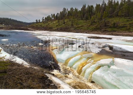 Spring landscape with a rushing stream and melting ice in South Yakutia Russia