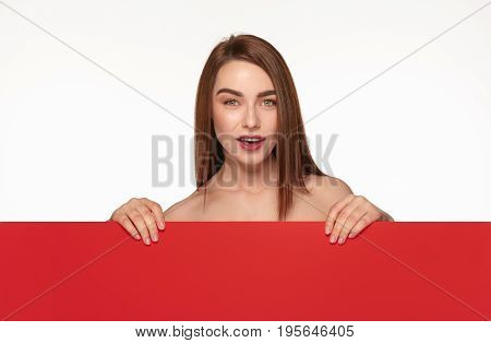 Young topless girl posing behind big piece of red cardboard on white background.