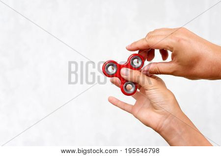 Fidget spinner. Red hand spinner, boys playing with fidgeting hand toy. Stress relief. Anti stress and relaxation adhd attention fad boy concept. Free space for text