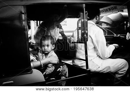 MUMBAI, INDIA - November 6 2017: A rickshaw driver and a family as passengers wait in heavy traffic in downtown Mumbai, India