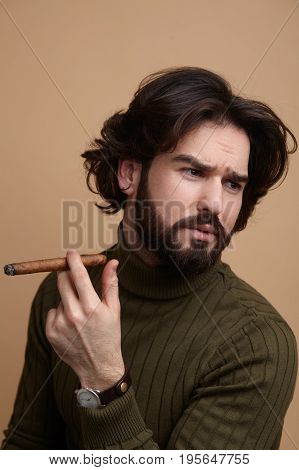 Handsome man in sweater holding cigar and looking away on studio background.