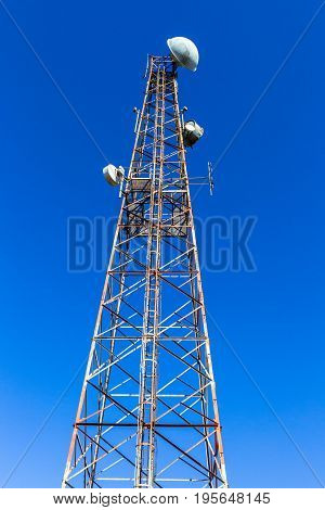 Steel tower against blue sky closeup vertical for radio tv signal communictions.