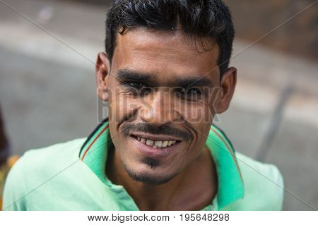 MUMBAI, INDIA - November 9 2017: A street seller with tobacco filled teeth smiles in Mumbai, India