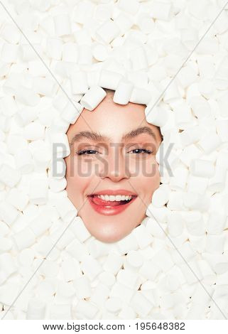 From above shot of young female face lying in fluffy marshmallow and smiling at camera.