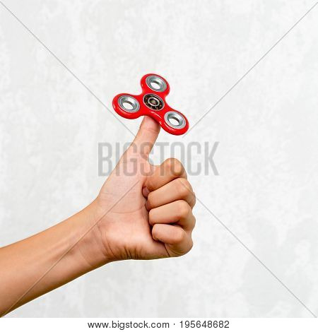 Fidget spinner. Red hand spinner, fidgeting hand toy rotating on child's hand. Stress relief. Anti stress and relaxation adhd attention fad boy concept