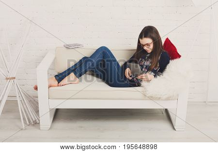Teenage girl in eye glasses look into tablet, lying on sofa. Children computer games, social networks and media addiction concept. Communication technologies, copy space
