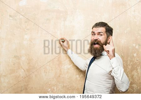 hipster man with long beard and hair on happy face in tie and white shirt write on textured beige wall background with chalk and raised finger copy space business and marketing education